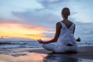 Woman in lotus position at sunset
